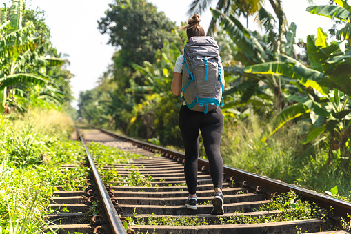walking on a railroad in a tropical location. young woman with big backpack. Sri lanka