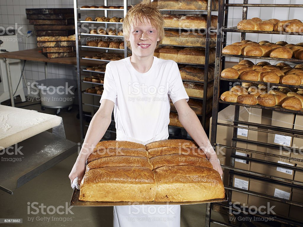 Young baker (14) carrying tray of fresh bread foto stock royalty-free