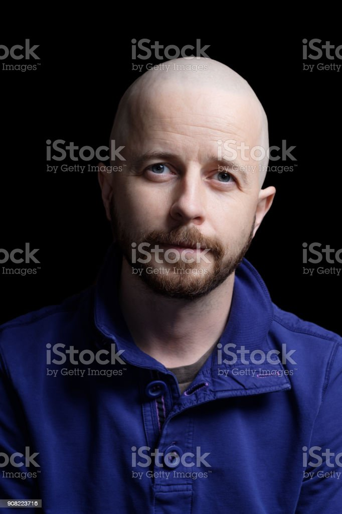 Young bald man in his 30s isolated on black background stock photo
