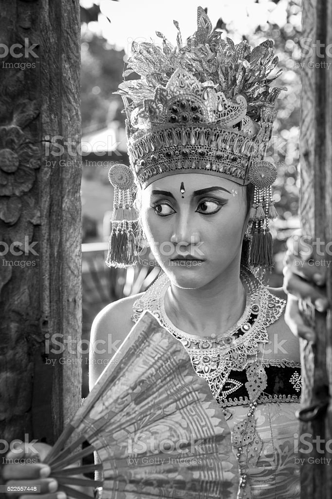 Young Bali dancer in traditional costume staring through a door stock photo