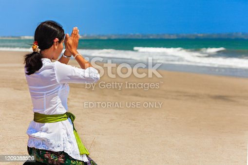 Bali island, Indonesia - March 18, 2015: Young balinese woman praying with namaste hands on sea beach at hindu ceremony before traditional religious holiday - silence day Nyepi.