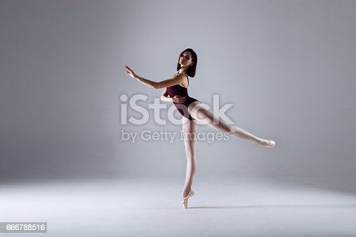 666789174 istock photo Young ballerina in a black dancing suit is posing on a grey background in the photostudio 666788516