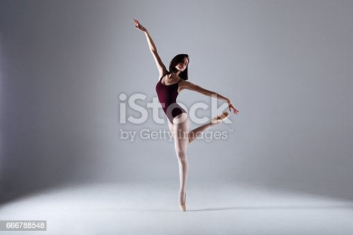 666789174 istock photo Young ballerina in a black dancing suit is posing on a grey background in the photostudio 666788548