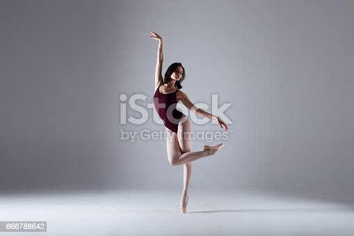 666789174 istock photo Young ballerina in a black dancing suit is posing on a grey background in the photostudio 666788642
