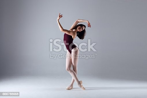 666789174 istock photo Young ballerina in a black dancing suit is posing on a grey background in the photostudio 666788668