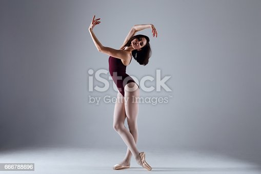 666789174 istock photo Young ballerina in a black dancing suit is posing on a grey background in the photostudio 666788696