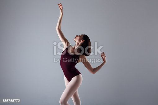 666789174 istock photo Young ballerina in a black dancing suit is posing on a grey background in the photostudio 666788772