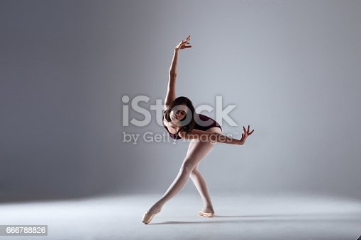 666789174 istock photo Young ballerina in a black dancing suit is posing on a grey background in the photostudio 666788826