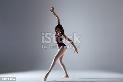 666789174 istock photo Young ballerina in a black dancing suit is posing on a grey background in the photostudio 666788902