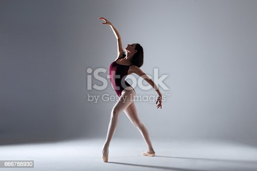 666789174 istock photo Young ballerina in a black dancing suit is posing on a grey background in the photostudio 666788930