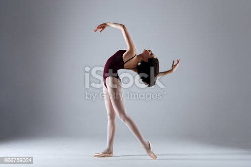 666789174 istock photo Young ballerina in a black dancing suit is posing on a grey background in the photostudio 666789024