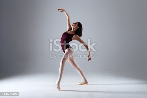 666789174 istock photo Young ballerina in a black dancing suit is posing on a grey background in the photostudio 666789056