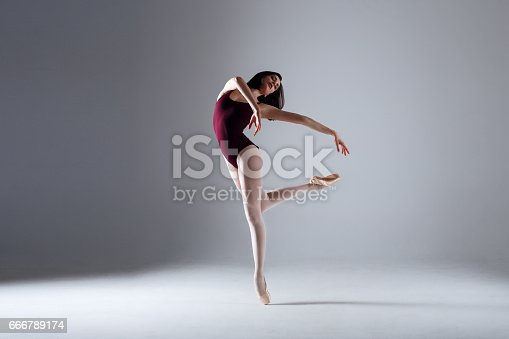 666789174 istock photo Young ballerina in a black dancing suit is posing on a grey background in the photostudio 666789174