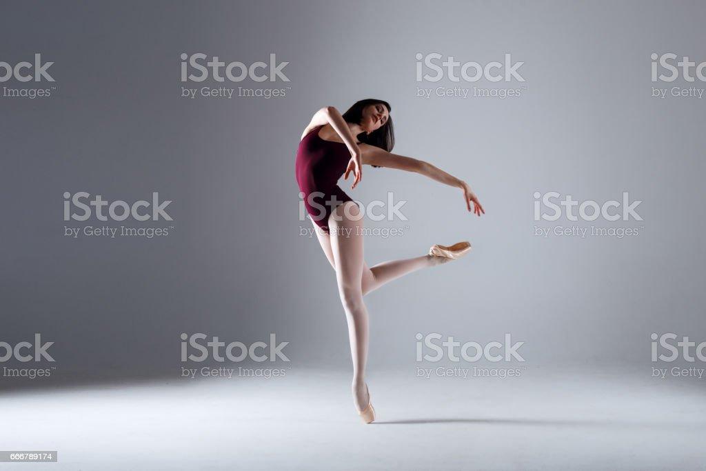 Joven bailarina de un negro traje de baile es posando sobre un fondo gris en el photostudio - foto de stock