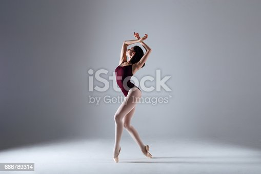 666789174 istock photo Young ballerina in a black dancing suit is posing on a grey background in the photostudio 666789314