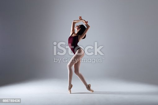 666789174 istock photo Young ballerina in a black dancing suit is posing on a grey background in the photostudio 666789406