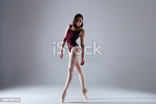 666789174 istock photo Young ballerina in a black dancing suit is posing on a grey background in the photostudio 666789446