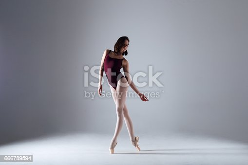 666789174 istock photo Young ballerina in a black dancing suit is posing on a grey background in the photostudio 666789594