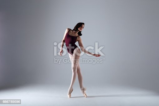 istock Young ballerina in a black dancing suit is posing on a grey background in the photostudio 666789596
