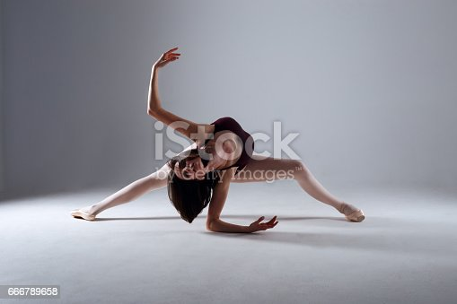 666789174 istock photo Young ballerina in a black dancing suit is posing on a grey background in the photostudio 666789658