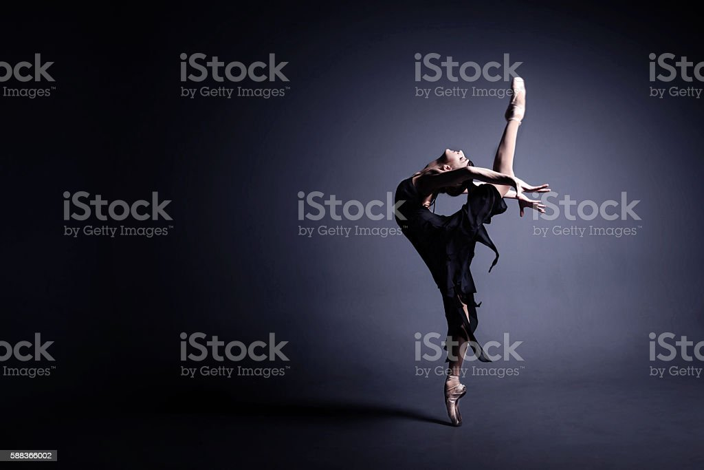 Young ballerina in a black suit is dancing in dark royalty-free stock photo