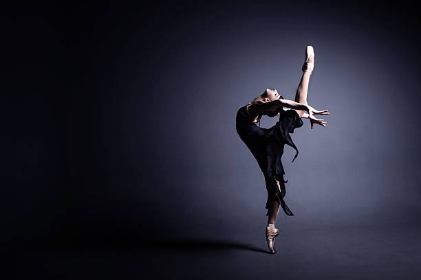 Young ballerina in a black suit is dancing in dark stock photo