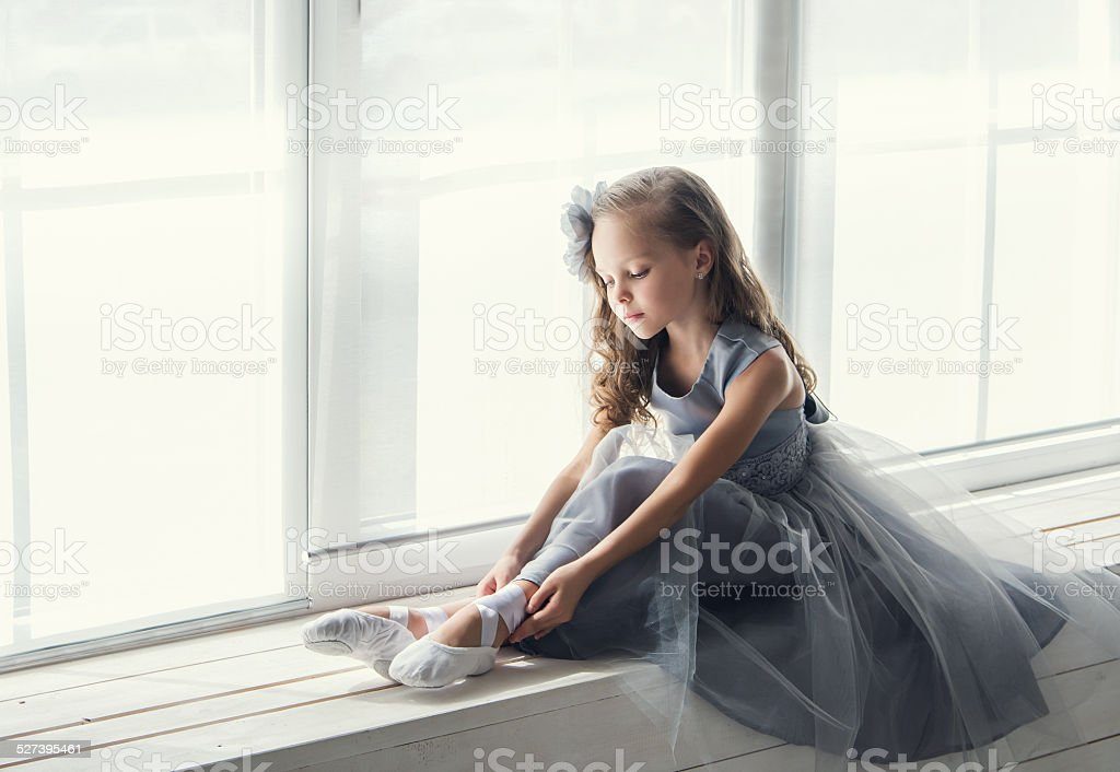 Young ballerina in gray dress puts on ballet shoes pointe stock photo