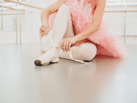 Young ballerina in pink tutu costume wraps white silk ribbons of soft top ballet shoes pointe and ties them up. Woman preparing for dance training lessons in gym