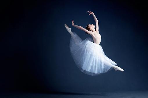 Young ballerina is dancing in a dark photostudio