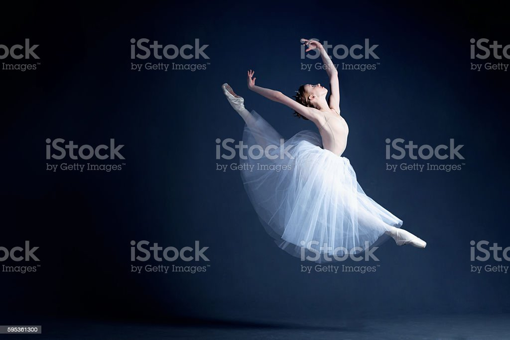 Young ballerina is dancing in a dark photostudio - foto de stock