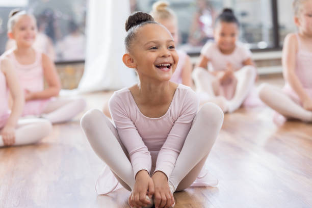 Young ballerina laughs at instructor's joke A cute laughing ballerina sits among classmates and listens to her instructor tell a funny joke during class.  She is grabbling her feet with knees bent to stretch while she listens. touching toes stock pictures, royalty-free photos & images