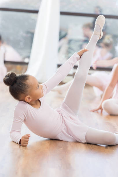 Young ballerina poses on floor with leg up during class stock photo