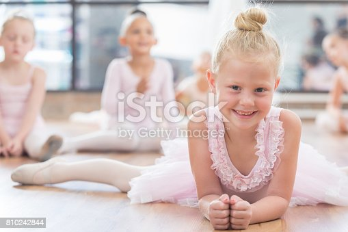 Sweet Caucasian ballerina leans on her elbows while doing the splits at her dance studio.  Other young ballerinas sit on the floor in the background.