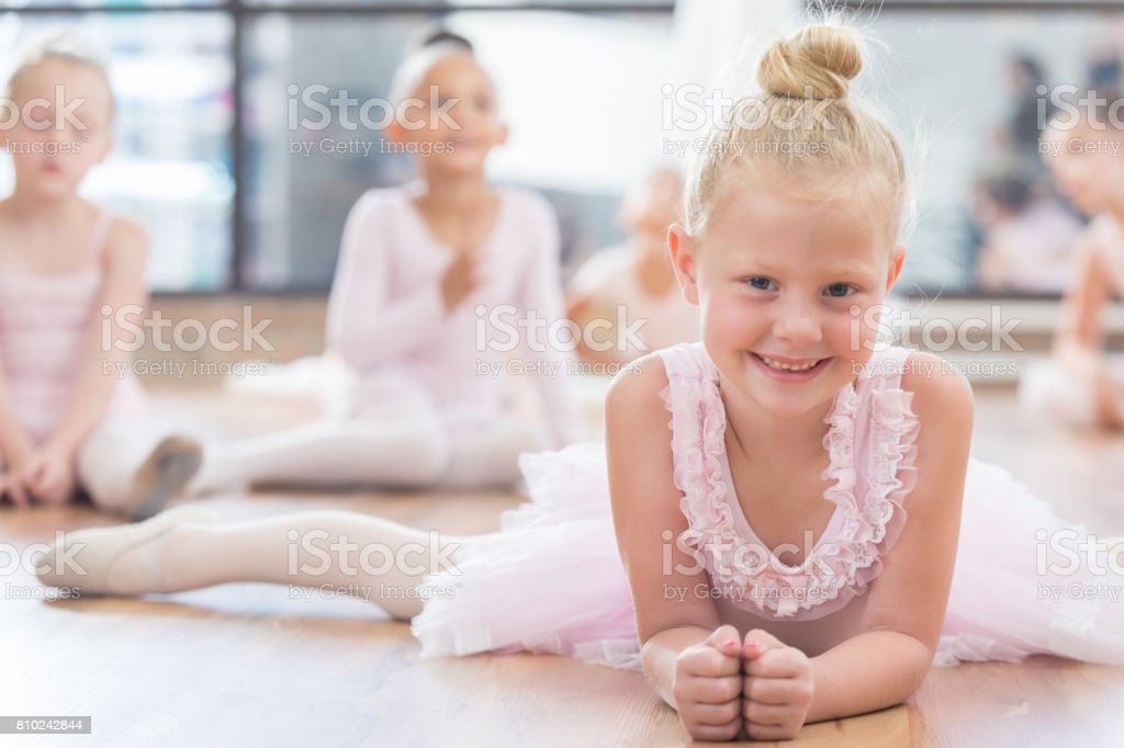 Young ballerina poses while doing the splits stock photo