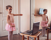 istock Young ballerina practicing classic choreography during online class in ballet school, self-isolation 1214106113