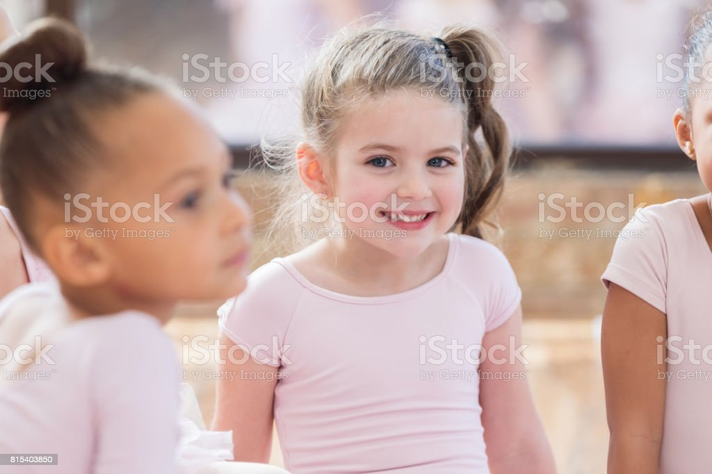 Young ballerina sits with friends and smiles during a class break stock photo