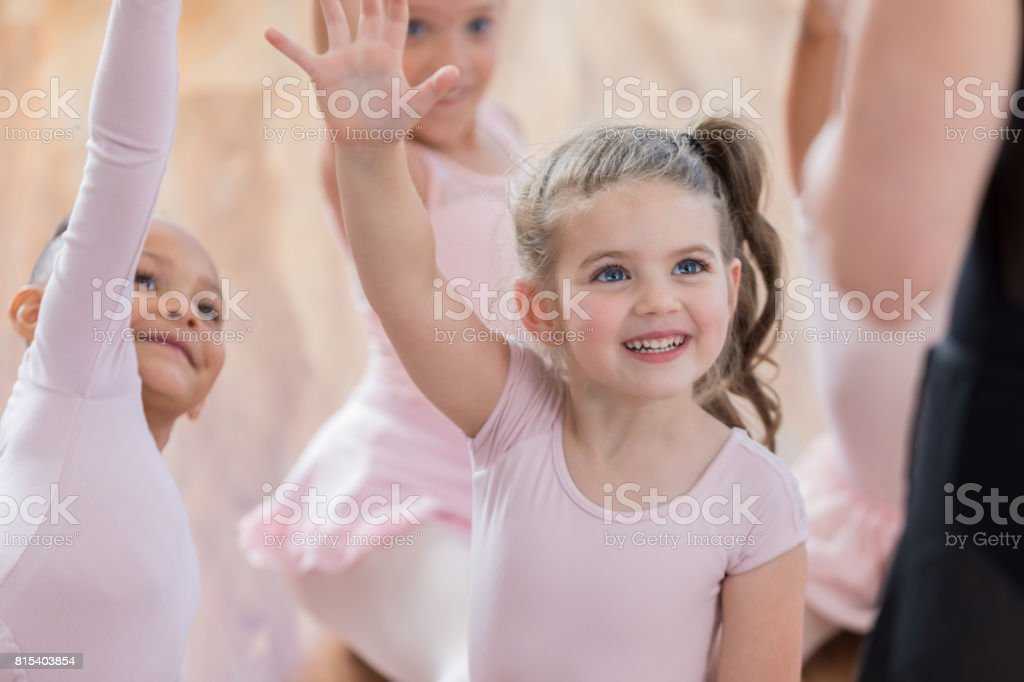 Young ballerina volunteers with friends to go first during class stock photo