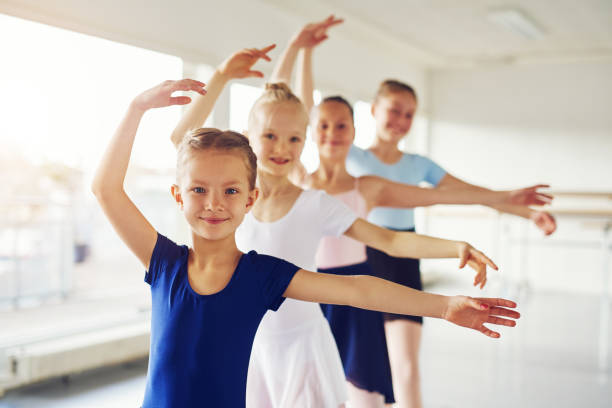 Young ballerinas dancing and looking at camera in class stock photo
