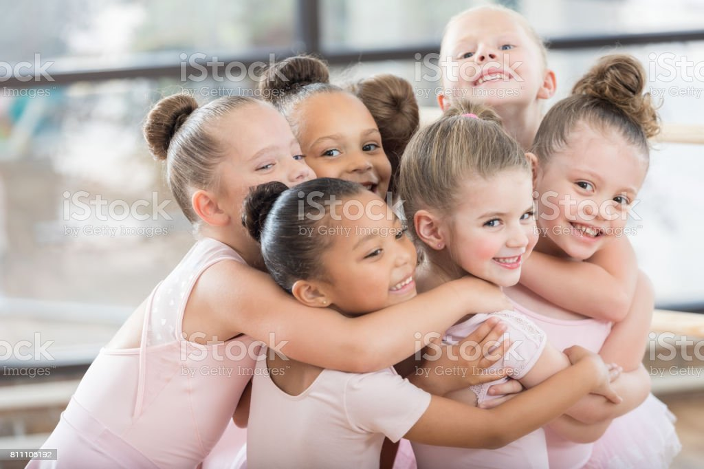 Young ballerinas form a smiling group hug stock photo