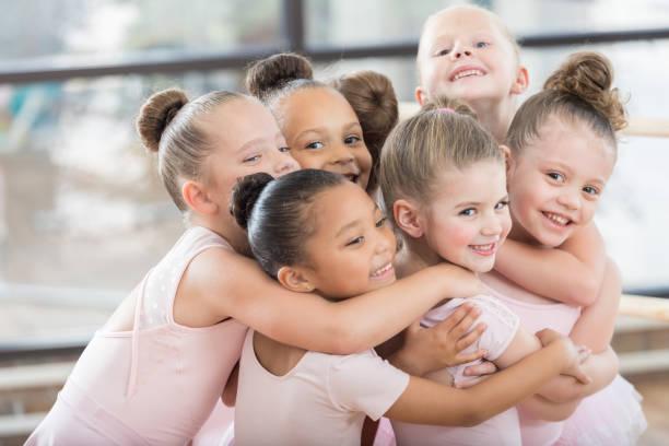 Junge Tänzerinnen bilden eine lächelnde Gruppe Umarmung – Foto
