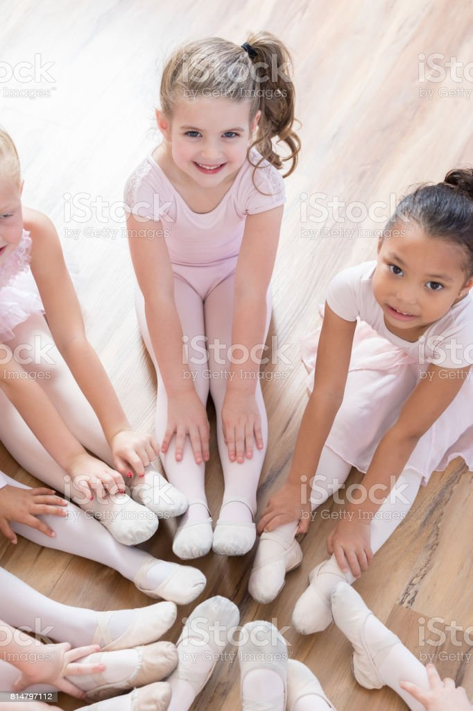 Young ballerinas look up at camera as they sit in circle with feet together stock photo