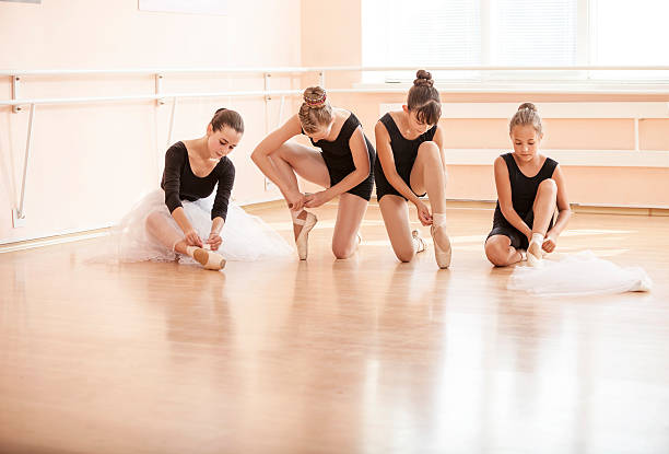 Young ballerinas putting on pointe shoes stock photo