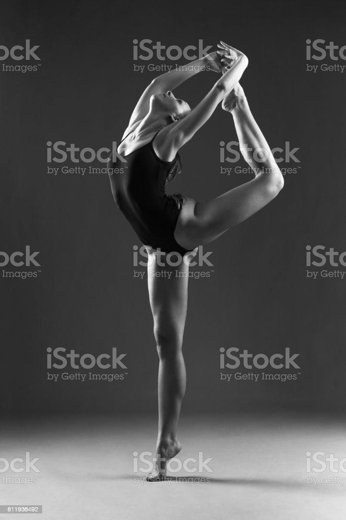 Young ballet dancer dancing in studio. She looks beautiful, muscular...