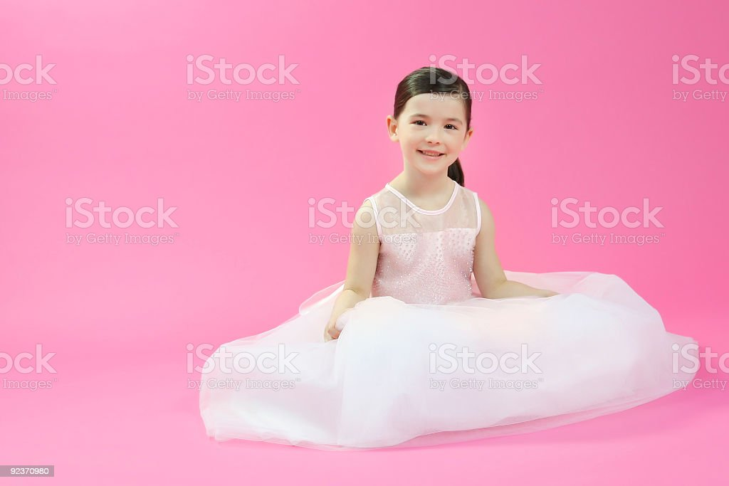 Young ballet dancer sitting on a pink background royalty-free stock photo