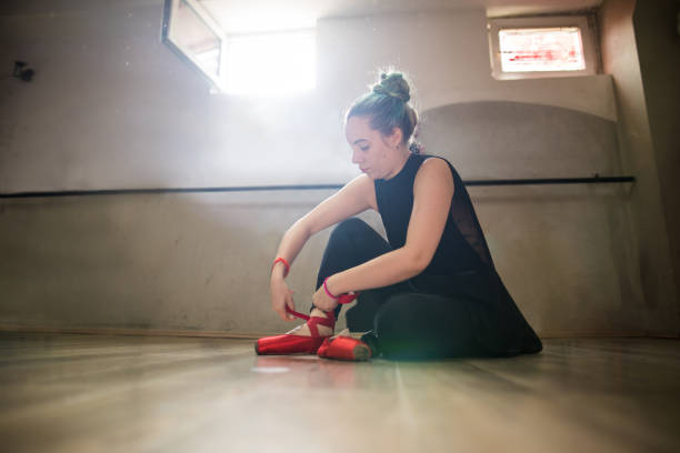 Young ballet dancer tying her red ballet pumps stock photo