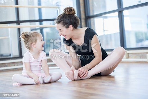 A young ballet instructor sits on the floor with her adorable young preschool age student as they look at each other and laugh while stretching.