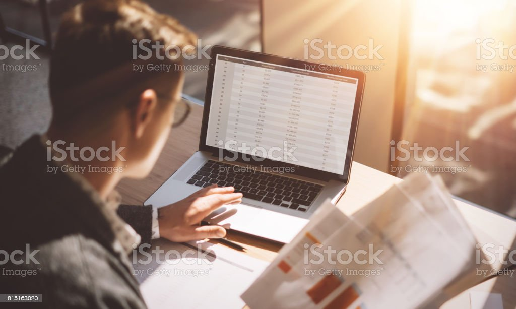 Young banking finance analyst in eyeglasses working at sunny office on laptop while sitting at wooden table.Businessman analyze stock reports on notebook screen.Blurred background,horizontal. stock photo