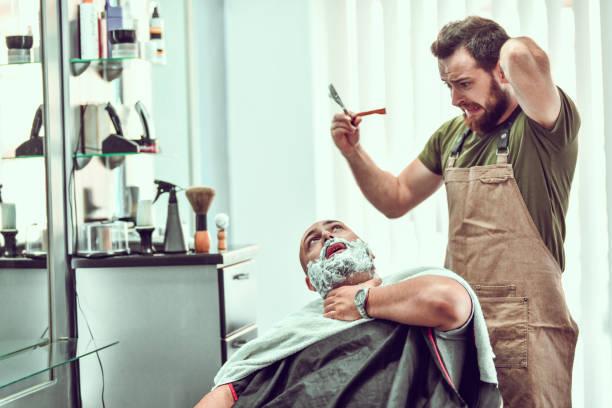 junge barbier macht fehler und schneidet kunden beim rasieren - cut wrong hair stock-fotos und bilder