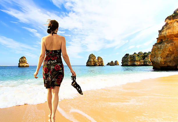 Young barefoot woman in dress  on the Rocky beach - foto de stock