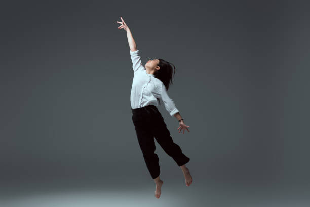 young barefoot woman jumping with raised hand on grey stock photo